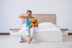 The young man waking up in bed. Young man waking up in bed Royalty Free Stock Photo
