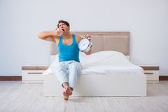The young man waking up in bed. Young man waking up in bed Royalty Free Stock Images