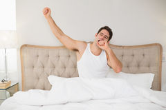 Young man waking up in bed and stretching arms Stock Photo