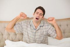 Young man waking up in bed and stretching his arms. At home Stock Photos