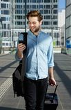 Young man walking at airport with bags and mobile phone Royalty Free Stock Photos