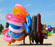 A young man walking along a beach with bunch of in. A young man overloaded with inflatable toys Royalty Free Stock Photo