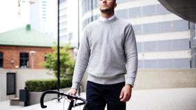 Young man walking along city street with bicycle stock video