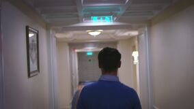 Young man walking along hallway corridor at home interior back view. Man back view walking on long corridor in cozy hotel stock video