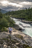 Young man walking along the mountanious river, Norway. Young man in grey sweatshirt is going along the rocks next to the mountain river. Forest on background and Stock Photos