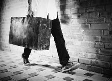 Young man walking along street with old suitcase. Black and white photo royalty free stock images