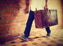 Young man walking along street with old suitcase, Royalty Free Stock Photo
