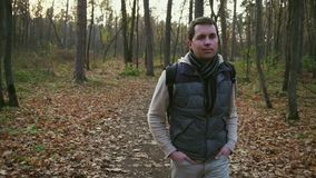 Young man walking in the autumn forest. Young guy walking in the autumn forest. He getting aesthetic pleasure while enjoying the autumn colors of the forest stock footage