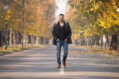 Young Man Walking In Autumn Forest. Young Man Walking In Forest Through The Woods Outside During Autumn Stock Image