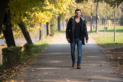 Young Man Walking In Autumn Forest. Young Man Walking In Forest Through The Woods Outside During Autumn Royalty Free Stock Photos