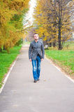 Young man walking in autumn park Royalty Free Stock Image