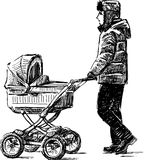 Young man walking with a baby carriage Stock Photo
