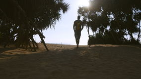 Young man walking with backpack along tropical beach to the ocean. Male hiker going at sandy shore to the sea. Backpacker stepping at shoreline during summer stock footage
