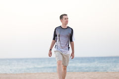 Young man walking on the beach Royalty Free Stock Photo