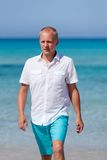 Young man walking on the beach in holiday Royalty Free Stock Images