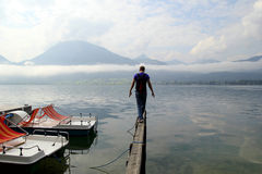 The young man are walking on a bridge with the view on the lake near to mountains in the cloudy weather. Royalty Free Stock Photo