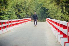 Young man walking on the bridge way unique photo stock images