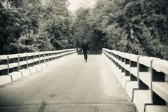 Young man walking on a bridge way royalty free stock images