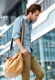Young man walking in the city with travel bag Stock Photos