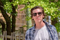Young man walking on college campus with sunglasses Stock Photography