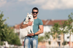 Young Man Walking Dog Outdoors In Summer Park. Young Man And German Spitz Walk In The Park - He Keeps The Dog On The Leash Royalty Free Stock Photo