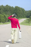 Young man walking down highway with empty gas can stock photo