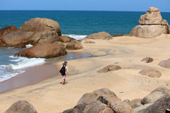Young man walking down a lonely beach lined with rocks and ocean Stock Photos