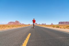 Young man walking down the Monument Valley road. stock image