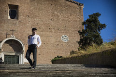 Young man walking down old stair in front of church in Rome, Italy Royalty Free Stock Photography