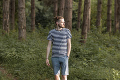 Young man walking in forest woods. Hard sunset light Royalty Free Stock Photo