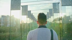 A Young Man Walking in a Glass Corridor. Medium Dolly shot Royalty Free Stock Images
