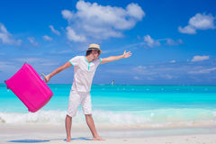Young man walking with his bag on tropical white beach Stock Images