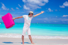 Young man walking with his bag on tropical white beach Royalty Free Stock Images