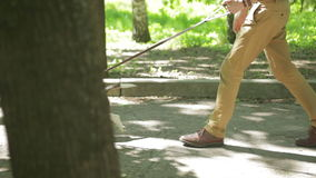 Young man walking with his dog in the park stock footage
