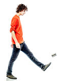 Young man walking kicking tin can  side view Stock Photos