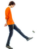 Young man walking kicking tin can  side view Stock Image