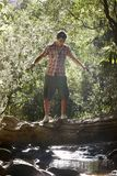 Young Man Walking On Log Over Stream Stock Photography