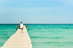 Young man walking on a long wood pier. And look over the ocean Stock Photo