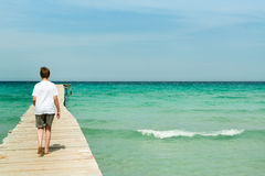Young man walking on a long wood pier. And look over the ocean Stock Photography