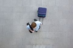 Young man walking with luggage at airport. Portrait from above of a young man walking with luggage at airport Stock Image