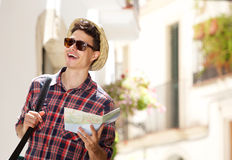 Young man walking with map and bag in town. Close up portrait of a young man walking with map and bag in town Stock Photos