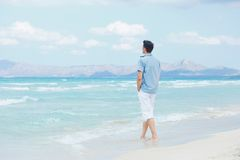 Young man walking near blue sea. Royalty Free Stock Photos