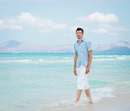 Young man walking near blue sea. Stock Photos