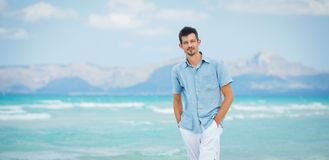 Young man walking near blue sea. Stock Photo