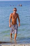 Young man walking in ocean water Royalty Free Stock Photo