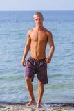 Young man walking in ocean water Stock Images