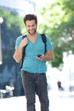 Young man walking outdoors with bag and mobile phone. Portrait of a cheerful young man walking outdoors with bag and mobile phone Stock Photography