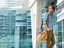 Young man walking outdoors with bag Royalty Free Stock Photography