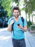 Young man walking outdoors with mobile phone. Portrait of a happy young man walking outdoors with mobile phone and earphones Stock Image