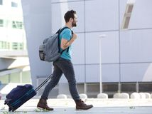 Young man walking outdoors with suitcase Stock Photos